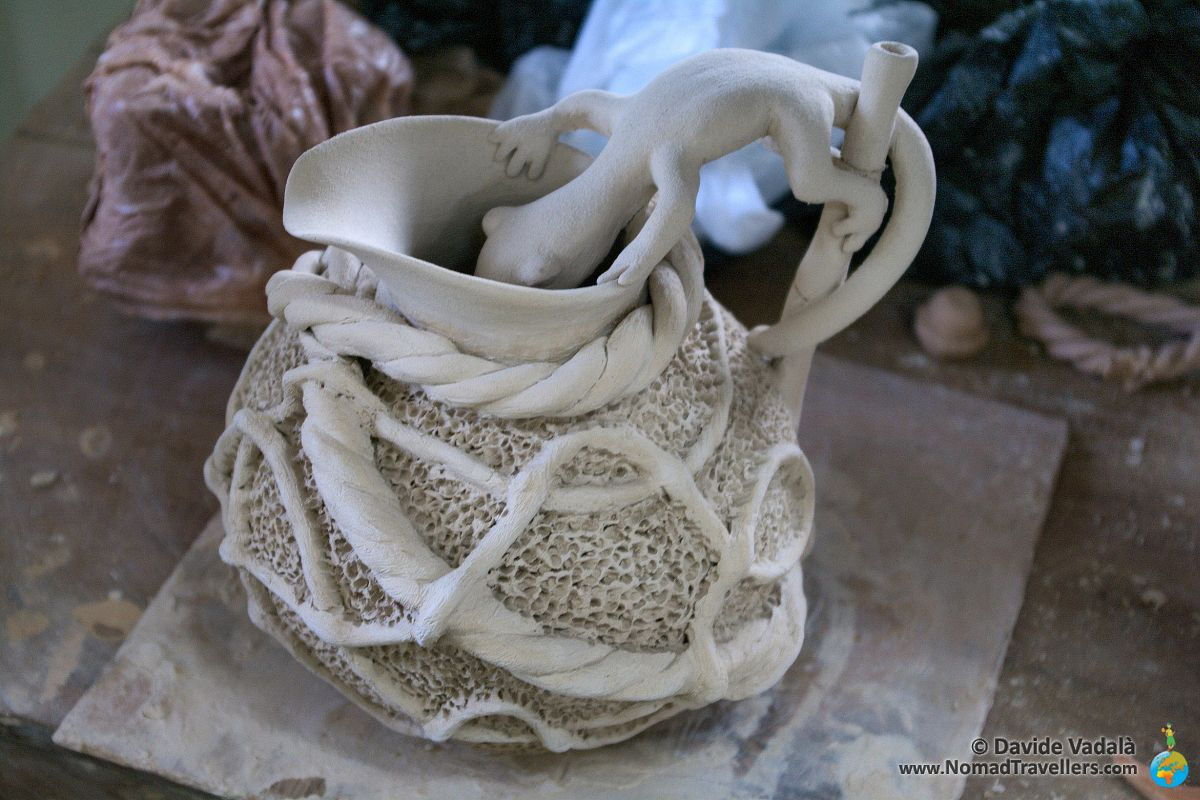 Pottery artwork: a gecko drinking from a pitcher