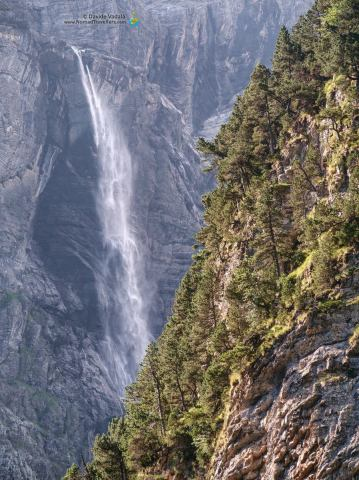 The waterfall appearing behind the side of the mountain