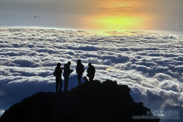 Climbers stand agaist the withe clouds and the orange sky on top of Mount Rinjani