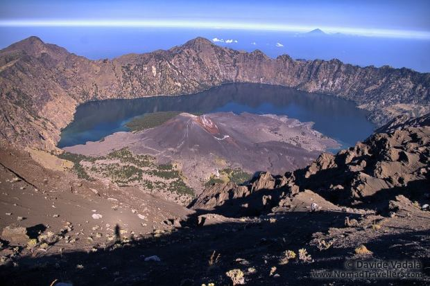 View of Segara Anak lake and its small crater from a lower altitude, with Gunung Agung on the background
