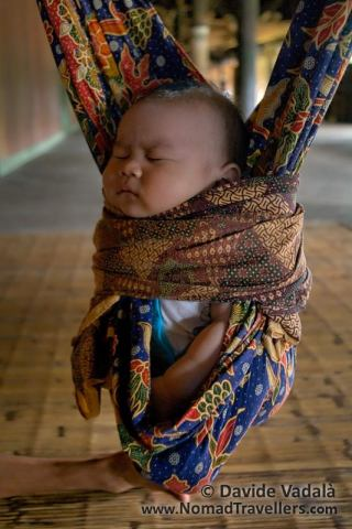 A Dayak kid sleeping on a spring swinging cradle in Eheng longhouse