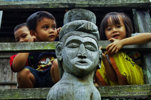 Kids peeping out behind a Dayak Hampatong wooden pole sculpture